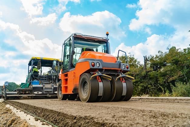 Machine om de grond te rammen en stoomwals voor asfalt lopen in de zomer door de weg