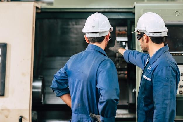 Machine onderhoud service engineer team samenwerken teamwerk in fabriek achteraanzicht.
