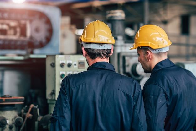 Machine service samen praten teamwerk werken in fabriek achteraanzicht.
