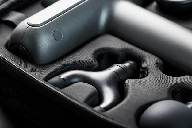 Machine voor lichaamsmassage in een koffer op zwart.