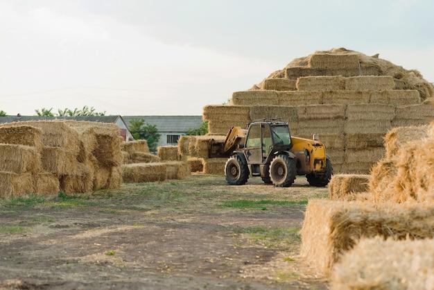 Machines stapelen hooibalen op boerderijgebied