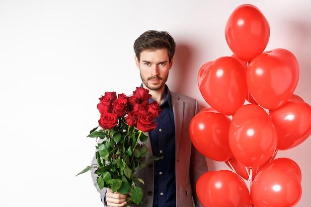 Macho man gaat op een romantische date, kijkt zelfverzekerd naar de camera, houdt cadeaus voor minnaar op valentijnsdag, permanent met hart ballonnen en rode rozen, witte achtergrond.