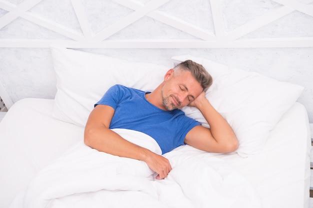 Macho met baard en snor verslapen wakker. ongeschoren man in de ochtend. goedemorgen voor jou. zoete dromen. man slapen in de ochtend. energie en vermoeidheid. man liggend witte slaapkamer.