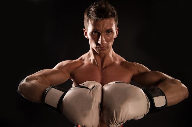 Macho met gespierde borst poseren met bokshandschoenen, zwarte achtergrond. sportman in bokshandschoenen toont zijn gespierde armen. atleet op zelfverzekerd gezicht toont gespierd lichaam. boksconcept.