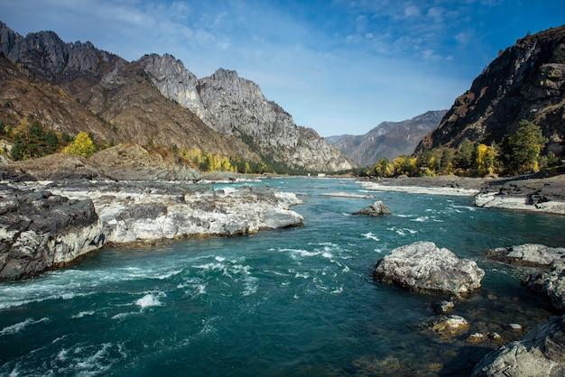 Machtige bergrivier stroomt langs steenachtige oevers tussen rotsachtige bergen tegen een heldere blauwe hemel.