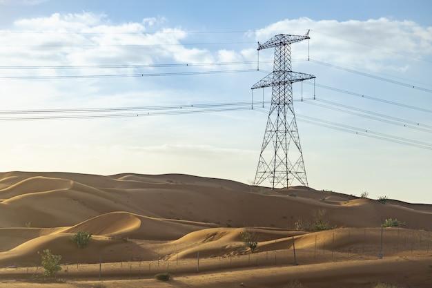 Machtslijnen met hoog voltage in woestijn in verenigde arabische emiraten op een achtergrond van blauwe hemel