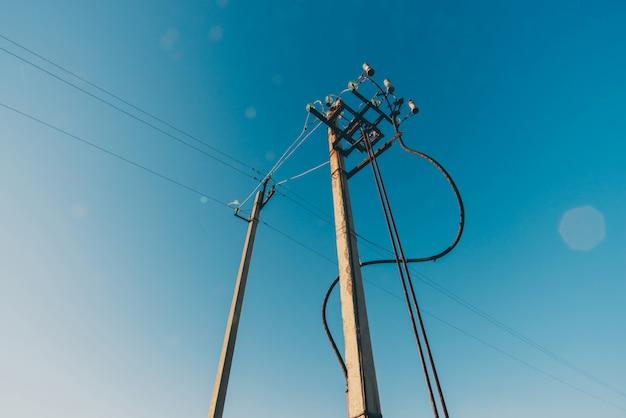 Machtslijnen van blauw hemelclose-up. elektrische hub op paal. elektriciteitsuitrusting met exemplaarruimte. draden van hoogspanning in de lucht. elektriciteitsindustrie.