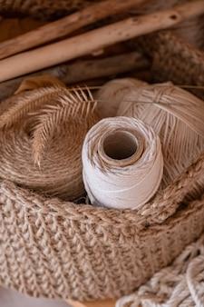 Macrame, katoen en hennep touwen in strengen. haken, opleveren van handwerkobjecten in een mand gemaakt van jute