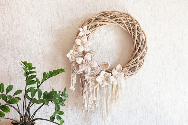 Macramékrans met grote katoenen bloem op een witte decoratieve gipsmuur. natuurlijk katoenen draad en touw. eco-decor voor thuis. creatieve wenskaart voor een creatief persoon.