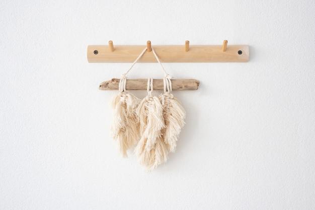 Macramepanelen hangen aan een houten haak aan een lichte muur.