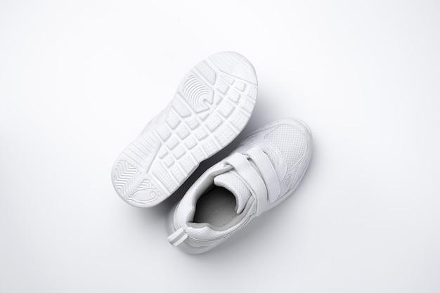 Macro bovenaanzicht twee witte unisex hardloopschoenen een hardloopschoen ligt zool omhoog geïsoleerd op witte achtergr...