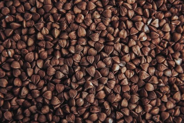 Macro foto eten boekweitgrutten. textuur achtergrond graan boekweit grutten. afbeelding voedingsproduct pap boekweitkorrels.