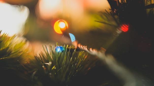 Macro getinte foto van gloeiende kleurrijke gloeilampen op kerstboomslinger