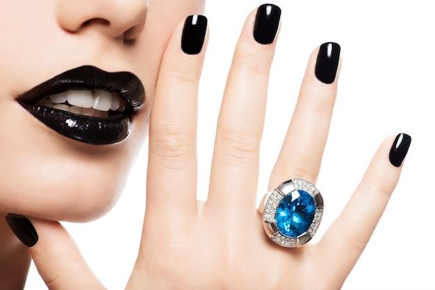 Macro-opname van de lippen en nagels van een vrouw geverfd felle kleur zwart