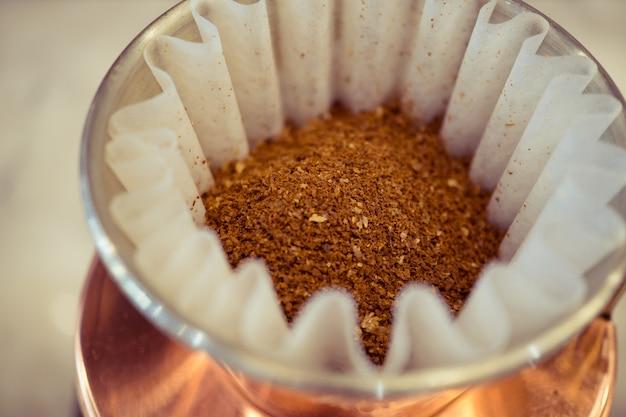 Macro-opname van droge gemalen koffie in druppelaar voor koffie brouwen