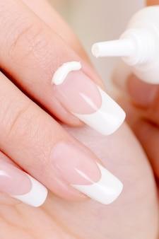 Macro-opname van een vrouwelijke wijsvinger met vochtinbrengende crème erop