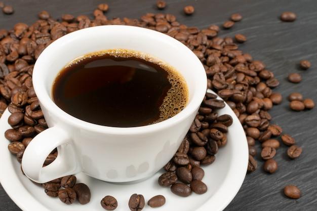Macro-opname van hete espresso-kopje en koffiebonen op zwarte stenen achtergrond.