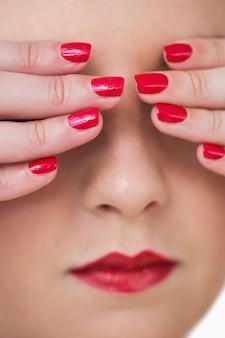 Macro-opname van jonge vrouw die betrekking hebben op ogen met rode geschilderde nagels