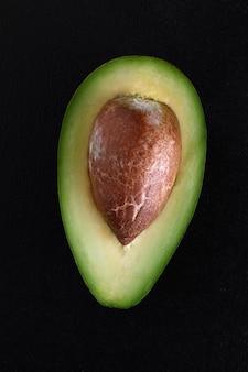 Macro-opname van verse avocado's in tweeën gesneden op de zwarte achtergrond.