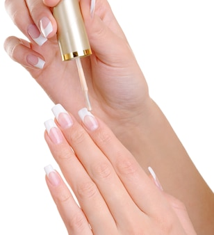 Macro-opname van vrouwelijke handen duidelijke nagel toe te passen verdwijnen op haar vingernagels