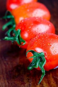 Macro-opnamen van vier natte tomaten close-up op houten tafel