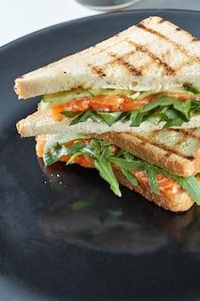 Macro sandwich met zalm op een zwarte plaat