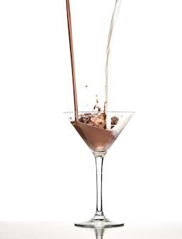 Macro shoot met warme chocolademelk vallen in glas op wit in studio