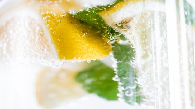 Macro van luchtbellen die in citroen en muntlimonade drijven met ijs.