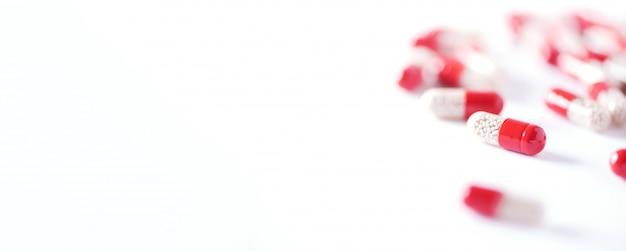 Macro van rode capsules op een witte achtergrond. kopieer ruimte. stelletje drugs, koude griepbehandeling.