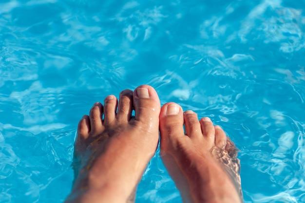 Macro vrouwen benen en tenen met een nette naakt pedicure in het helderblauwe water van het zwembad op een hete zon...