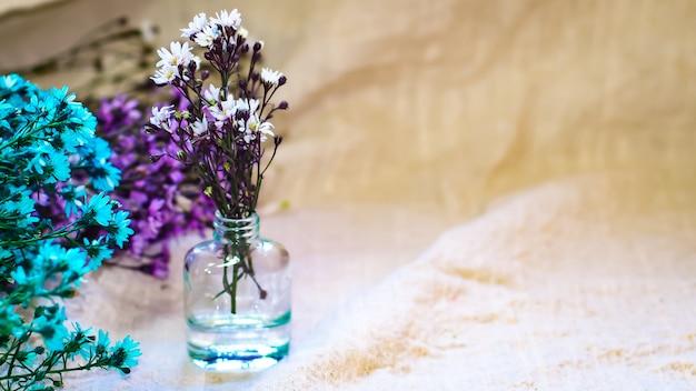 Macro witte blauwe violette flowesr in een kleine fles op een achtergrond van het natuurlijke linnen