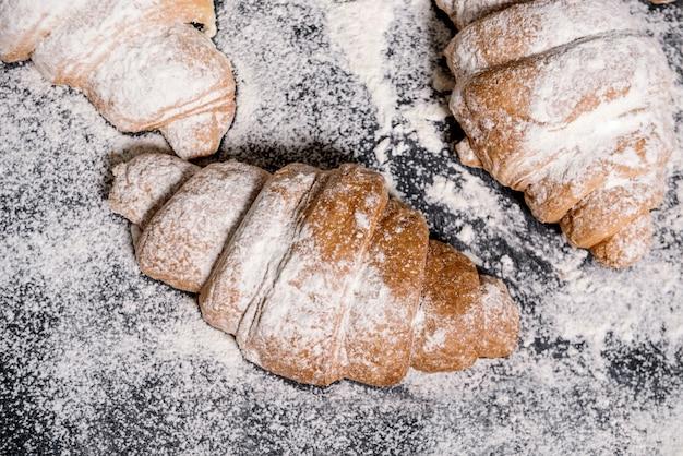 Macrobeeld van croissants met poedersuiker op grijze lijst.