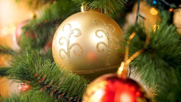 Macrobeeld van glinsterende en sprankelende gouden kerstbal die aan de kerstboomtak in de huiskamer hangt