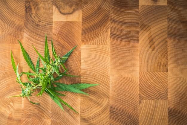 Macrofoto's van marihuanainstallatie met bladeren en toppen op houten oppervlak.