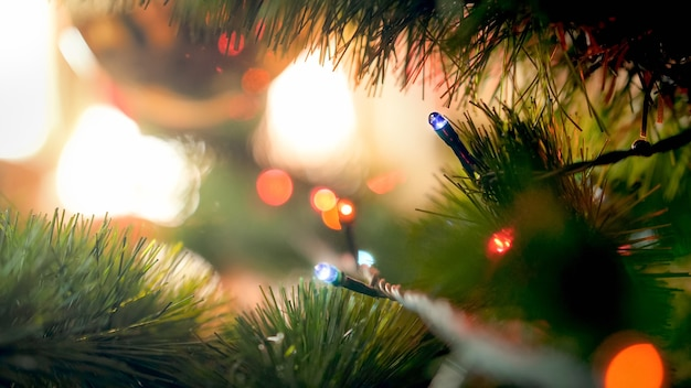 Macrofoto van gloeiende kerstboomverlichting op dennenboomtak