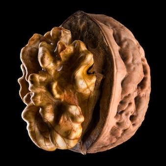 Macrofoto van half geopende walnoot met pit met bezinning over een zwarte achtergrond. geïsoleerd met uitknippad.