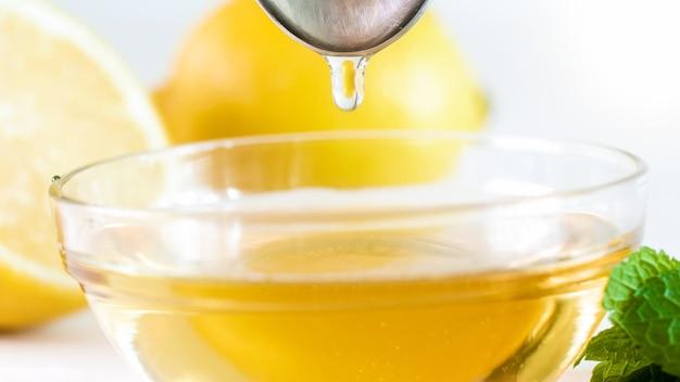 Macrofoto van honingdruppel die van lepel valt.