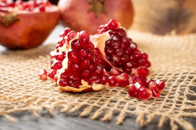 Macrofoto van vers rijp organisch granaatappelfruit met sappige zaden op rustieke tafellakenjute
