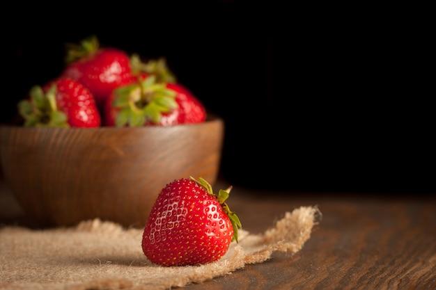 Macrofoto van verse rijpe rode aardbei in een houten kom op rustieke achtergrond. biologische natuurlijke producten.