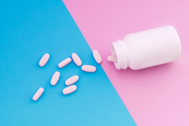 Macrofotopillen die uit een witte fles op een pastelkleurige achtergrond uitgieten. pillen op roze en blauwe achtergrond