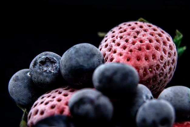 Macromening van bevroren bessen: aardbei, bosbes met ijsblokjes