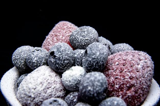 Macromening van bevroren bessen: aardbei, bosbes op donkere achtergrond