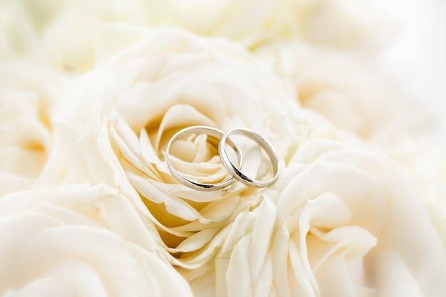 Macromening van twee platinatrouwringen die op witte rozen liggen