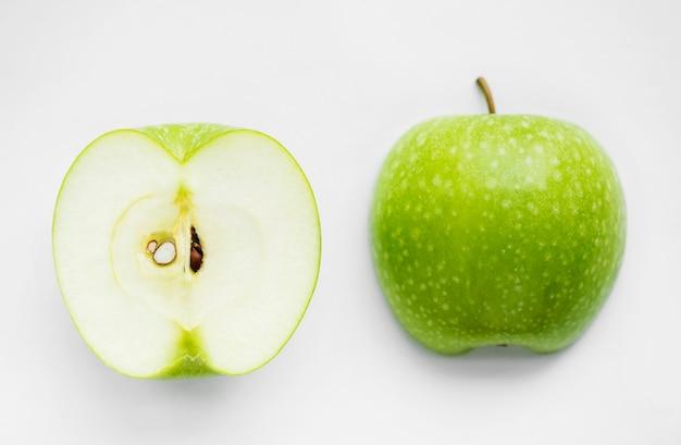 Macroschot van groene die appel op witte achtergrond wordt geïsoleerd