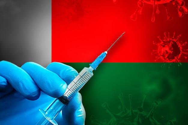 Madagascar covid19 vaccinatiecampagne hand in een blauwe rubberen handschoen houdt de spuit voor de vlag