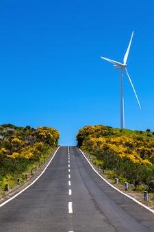 Madeira eiland. weg naar de blauwe lucht met een windturbine. vakantie