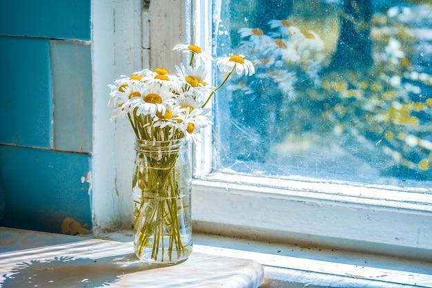 Madeliefjes in een glazen pot bij een raam, filter of effect