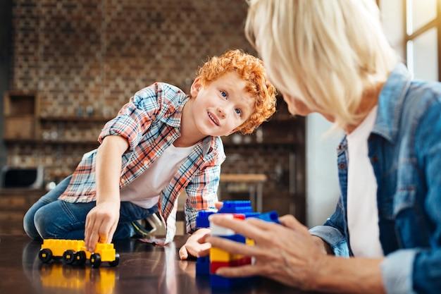 Mag ik je iets vragen. selectieve aandacht voor een nieuwsgierige roodharige jongen die op een tafel zit en met een lichte glimlach naar zijn grootmoeder kijkt