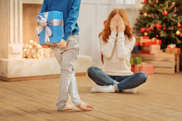 Mag ik mijn ogen al openen. selectieve focus op een verlegen doosje dat een mooi cadeau achter zijn rug verbergt terwijl hij zijn moeder een heel vrolijk kerstfeest wenst.