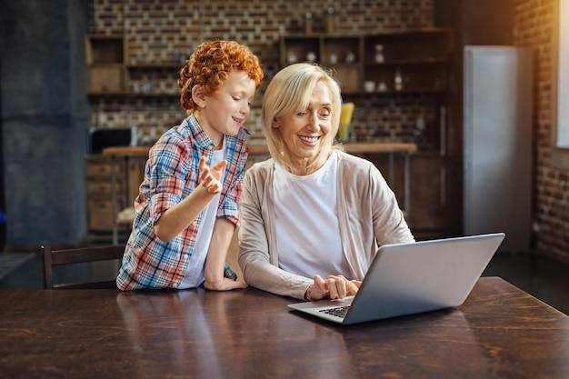 Mag ik proberen. liefdevolle senior dame kijken naar een scherm van haar laptop terwijl ze luistert naar haar kleinzoon gekrulde haren praten over computers.